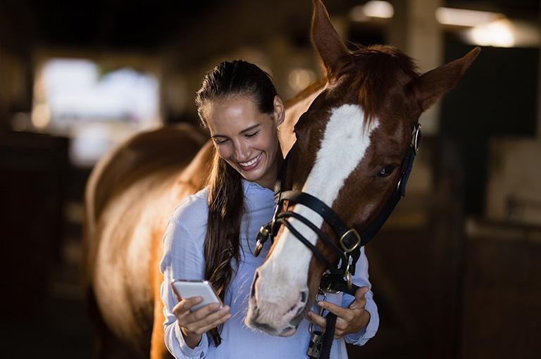 kobieta ztelefonem stojąca obok konia